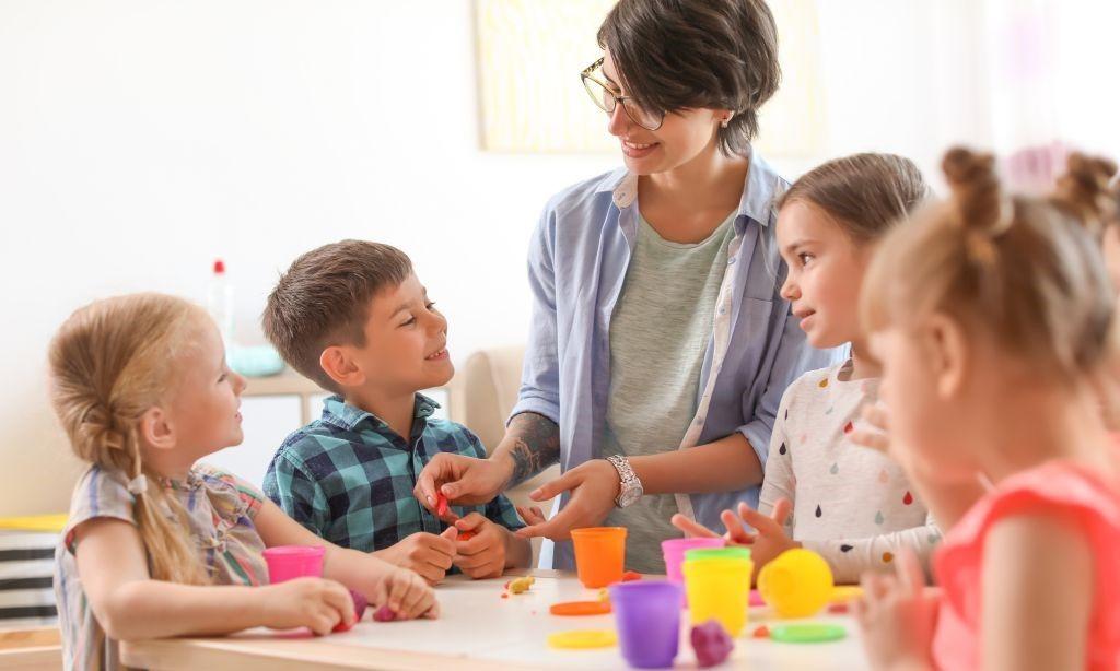 Vier Kinder spielen mit ihrer Kindergärtnerin mit Knetmasse.